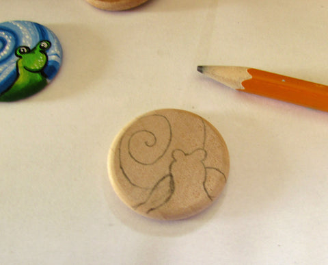 drawing the snail shell and head onto the wooden round with a pencil