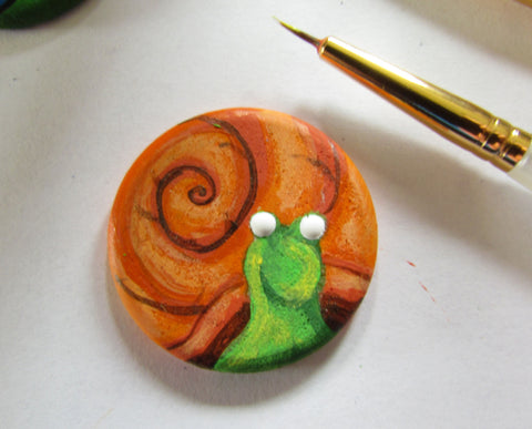detailing the painted eyes onto the wooden snail magnet in this how to paint a snail diy tutorial