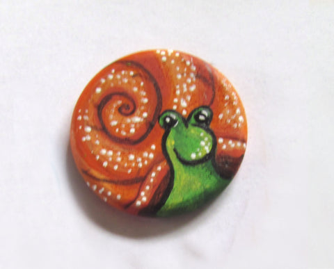finishing the fine details of paint painted onto the wooden snail magnet in this how to paint a snail diy tutorial