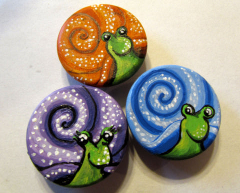 orange, blue and purple wooden snail magnets painted by Canadian artist Miriam Handfield