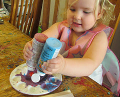 Teaching a young toddler all their colours by letting them have hands on experiences. Toddler pouring red and blue acrylic paint to mix into purple.