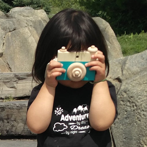 Child pretending to take a photo with a teal custom colour MDH Toys wooden camera.