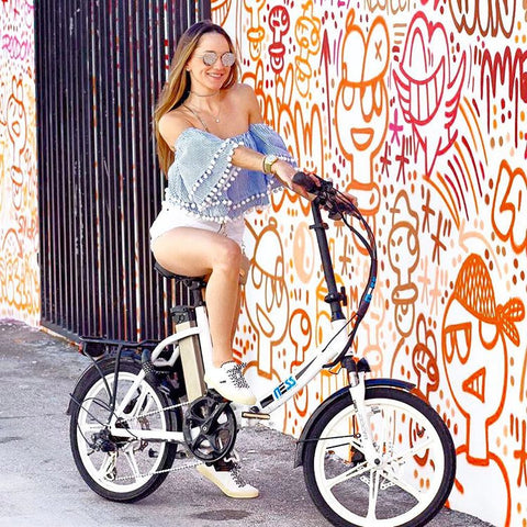 ness folding electric bikes young woman sitting on ebike next to colorful wall art