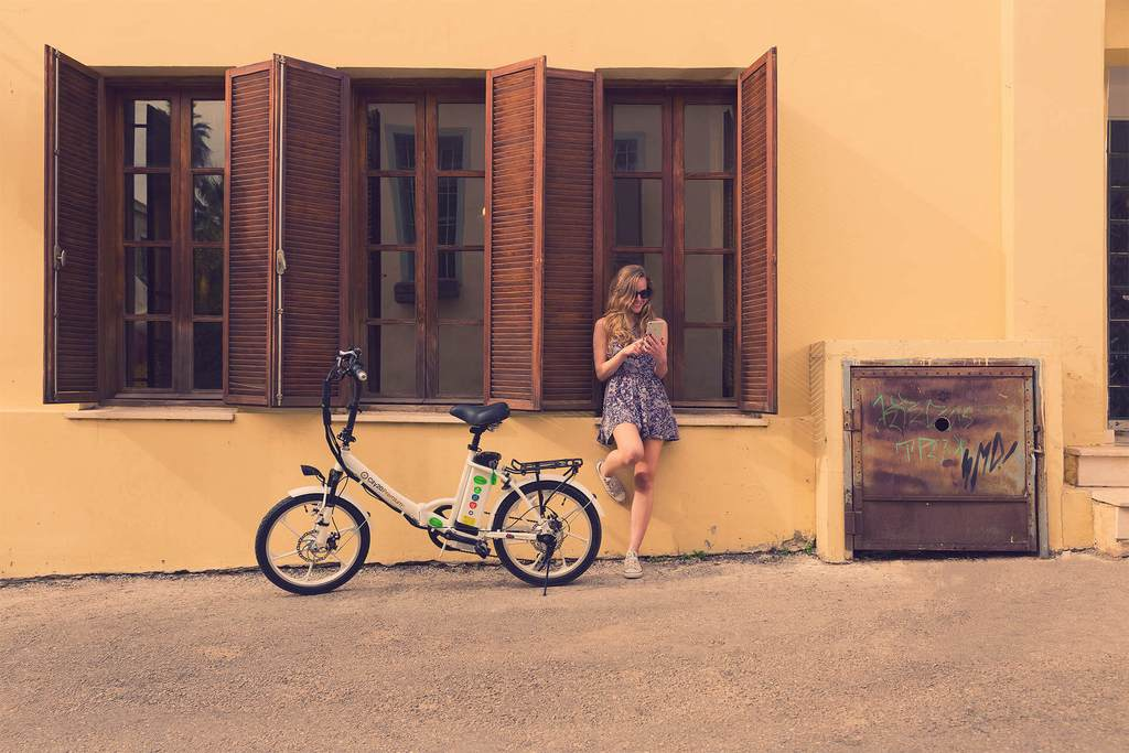 young woman standing next to folding ebike