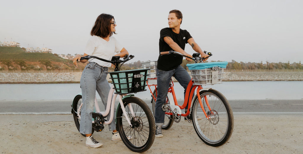 young couple outside riding bikes from the electric bike company