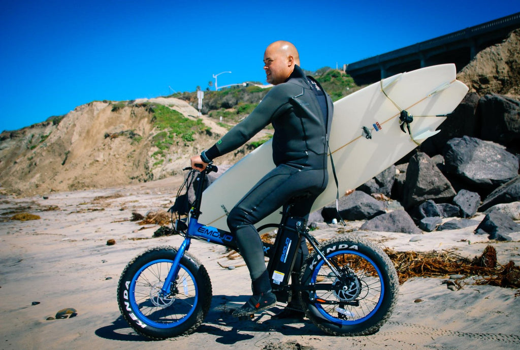 emojo lynx folding ebike with surfer guy at beach
