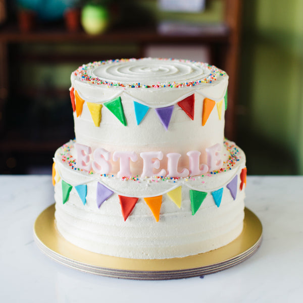 Two-Tier White Striped Cake with Fondant Rainbow Bunting - Custom Bakes by Edith Patisserie