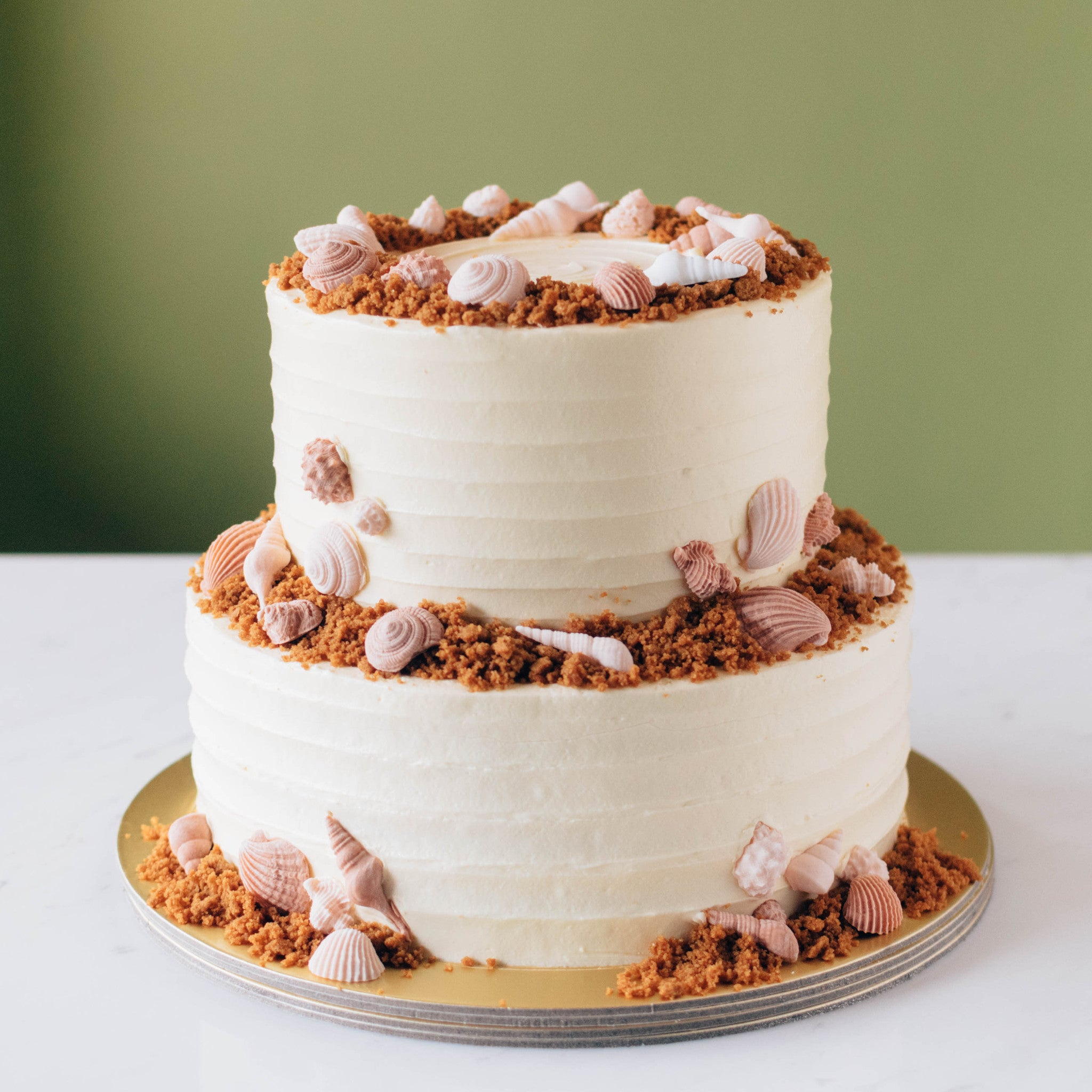 Two-Tier White Striped with Crumble and Seashells - Custom Bakes by Edith Patisserie