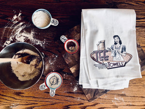 Classic vintage flour sack tea towel with baking supplies and kitchen supplies.