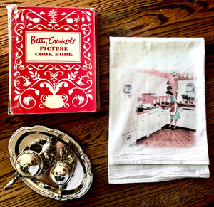 Classic vintage flour sack tea towel with tea set and betty crocker cookbook. Cute old fashioned kitchen supplies.