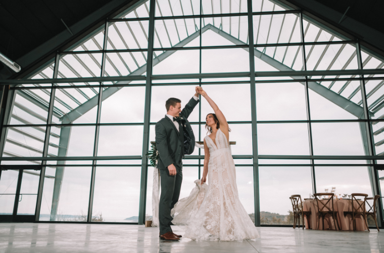 Couple dancing by glass wall in Cedar Pavilion large wedding venue. Photo by Nicolette Sessin Photography. Hair: Platinum & Co. Dress/Tux: Celebrations of the Heart. Rentals: All About You Event Planning & Rentals.