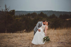 Wedding couple kiss with beautiful Flint Hills in the background at Blue Vista. Photo Credit: Megan Thornton / Demiurge Photography