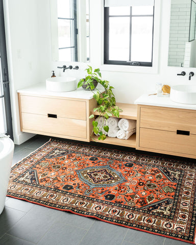image of vintage caucasian rug with deep reds and blues infront of bathroom sink, his and hers