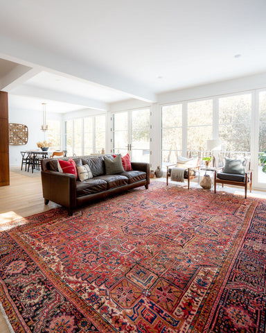 very large vintage Persian area rug that is mainly red, in front of leather couch in open concept living room
