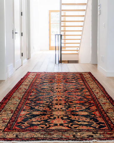 vintage Persian area rug in a open and airy hallway, with see through staircase