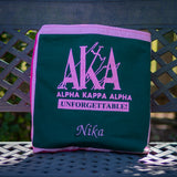 Quillow for the sorority Alpha Kappa Alpha, folded for use as a pillow, with name embroidery