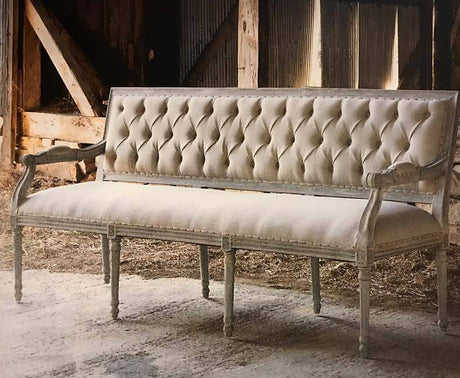 elegant tufted banquette bench with cream upholstery and pale washed oak wood