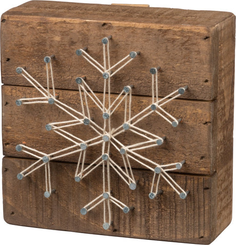 wooden block with snowflake string art