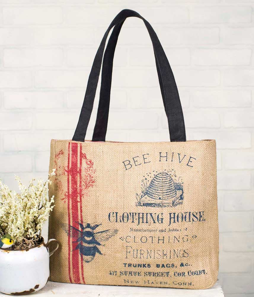 burlap tote bag with red stripe along side and blue text reading Bee Hive Clothing House, along with image of bee hive and bumble bee
