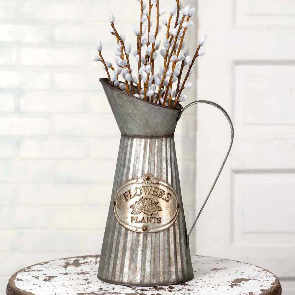 tall galvanized metal pitcher with flowers and plants tag