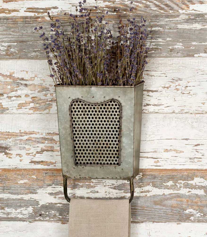 grater used as wall decor with towel rod and flower arrangement