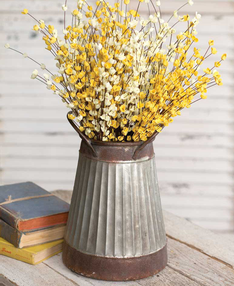 corrugated metal pail with yellow and white flowers