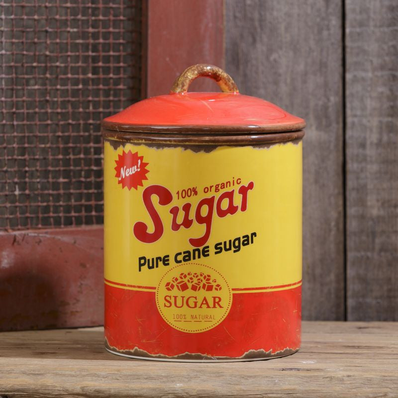 "Sugar canister with yellow and orange-red retro design and ""sugar"" written across front"