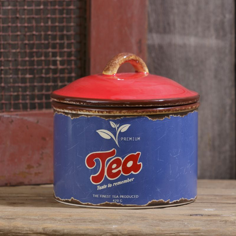 "Tea canister with blue and red retro design with pale blue tea leaves and ""tea"" written across front"