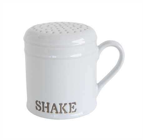 "off white stoneware shaker with handle and embossed word ""shake"" in capital letters toward bottom"