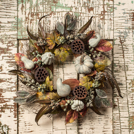 wreath with muted white pumpkins and pheasant feathers