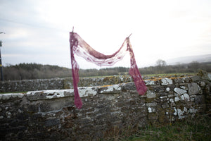 a lace shawl is hung on a washing line, light shines through.