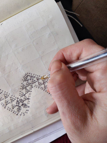 a hand draws a chart in a notebook