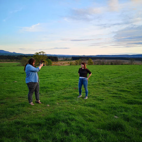 two women stand in a field, one is photographing the other