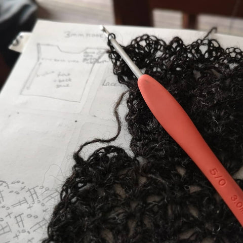 a swatch and hook sit on top of an open design journal showing a hand drawn schematic and crochet chart