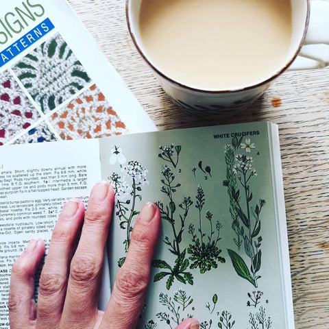 a cup of coffee and stitch dictionary lie on a table with a hand holding open a botanical reference guide