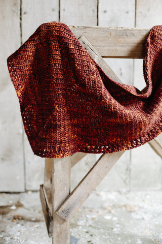 brown thick shawl rests on a carpentry support in a wooden barn