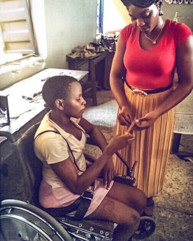 Chimsom Akah hand-braiding leather for NSAATA shoes, being assisted by a classmate in a wheelchair, at the Friends of the Disabled Centre, Lagos, Nigeria