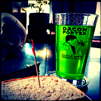 A Dagon Porter glass filled with green liquid sits on a table near a sandwich