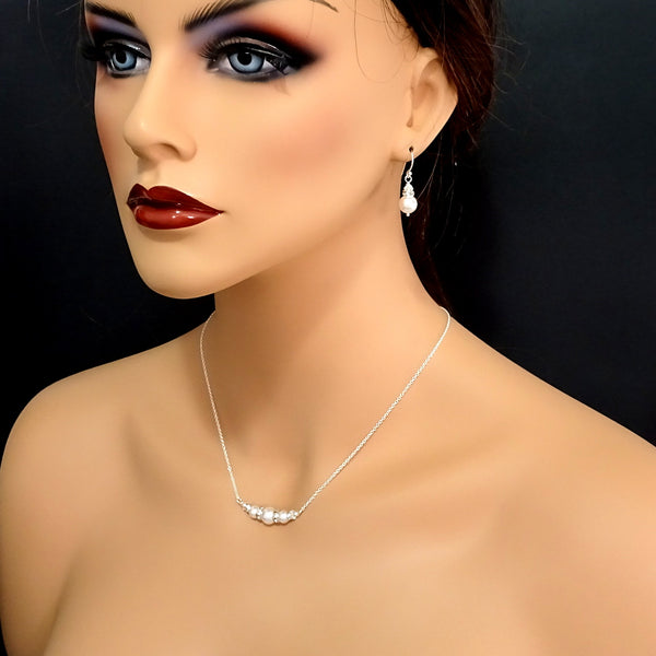 ivory pearl and clear crystal necklace and earrings set on a model mannequin