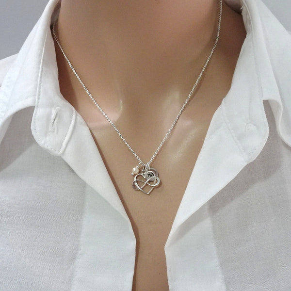 heart infinity necklace with ivory pearl and initial charm on a model mannequin