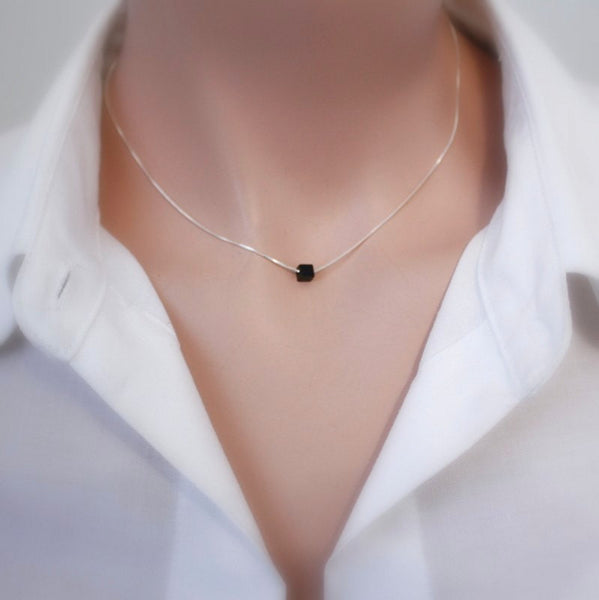 tiny black onyx cube necklace on a model mannequin