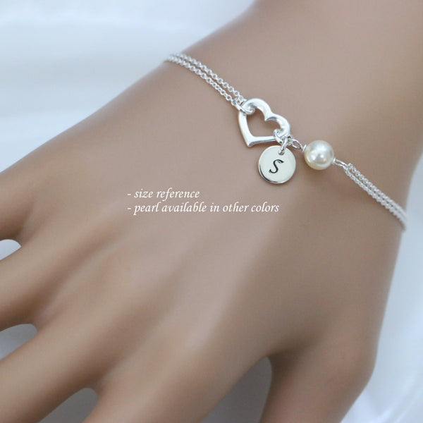 open heart and white pearl bracelet with initial charm on a model