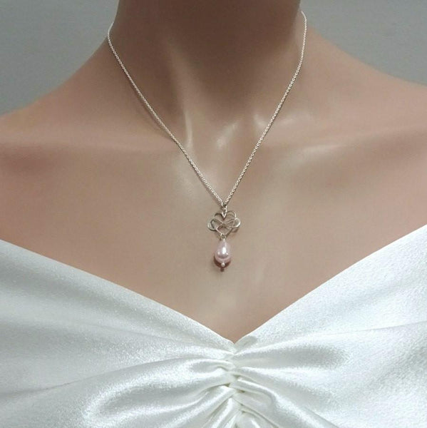 infinity heart and light pink pearl necklace on a model