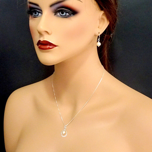 infinity and pearl necklace and earrings set on a model mannequin