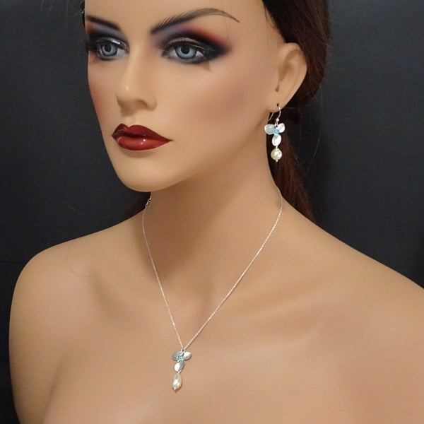 orchid, pearl and crystal earrings on a model