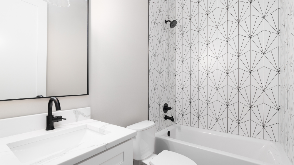 A matte black shower head and black bathroom fixtures in a white bathroom