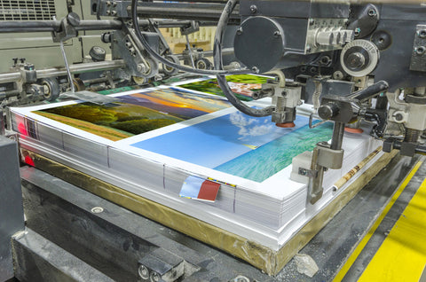 offset machine press print run at table, sheet-fed paper feeder unit. Poster printing