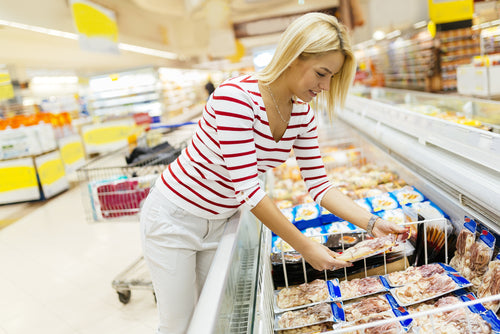 woman shopping choosing frozen food in supermarket