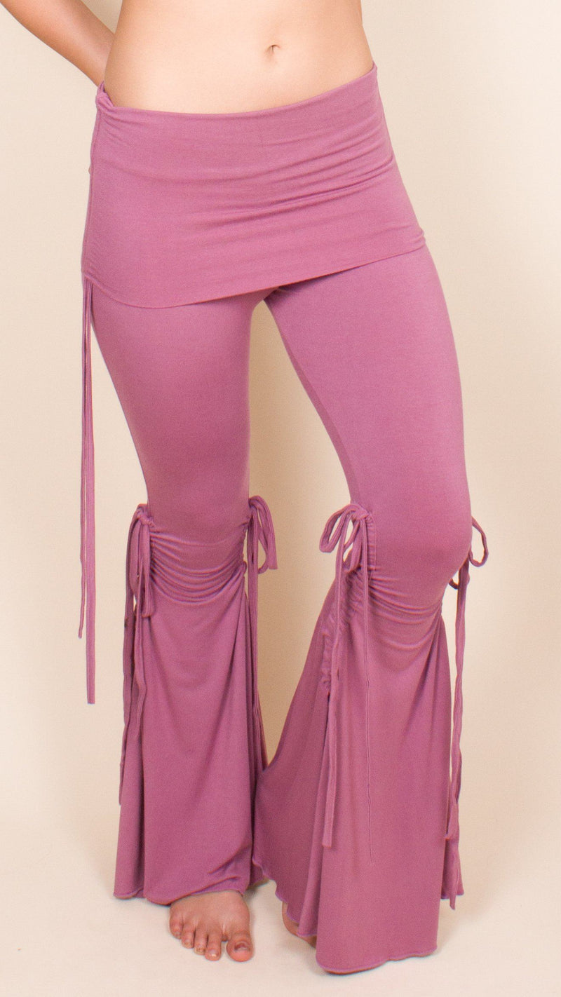 Girl wearing Umba's Bell Bottom Tie Pants with fold over skirt waistband and cinched ties on inner and outer legs and hips, dusty rose, front side view, sold at UMBA LOVE.
