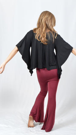 Girl wearing Umba's black Butterfly Sleeve Top with maroon fold over pants, back view, festival fun, sold at Umba Love in Boulder, CO